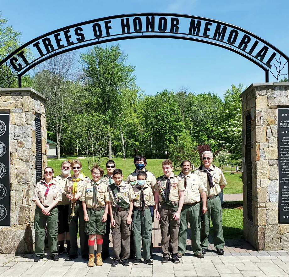 Middletown Boy Scout Troop 41 members placed an American flag on each of the 65 trees planted at the Connecticut Trees of Honor in Middletown in honor of Memorial Day at Veterans Memorial Park. From left are Joe Ternullo, assistant scoutmaster,  Jakob Beck, Zack Minor, Ben Curiel, Brian Masselli, Andrew Myer, Jack Hoover, Scoutmaster Ed Myer, taps player Michael Kline and his father, Dan Kline, a veteran. Photo: Tami Kapacziewski / Contributed Photo