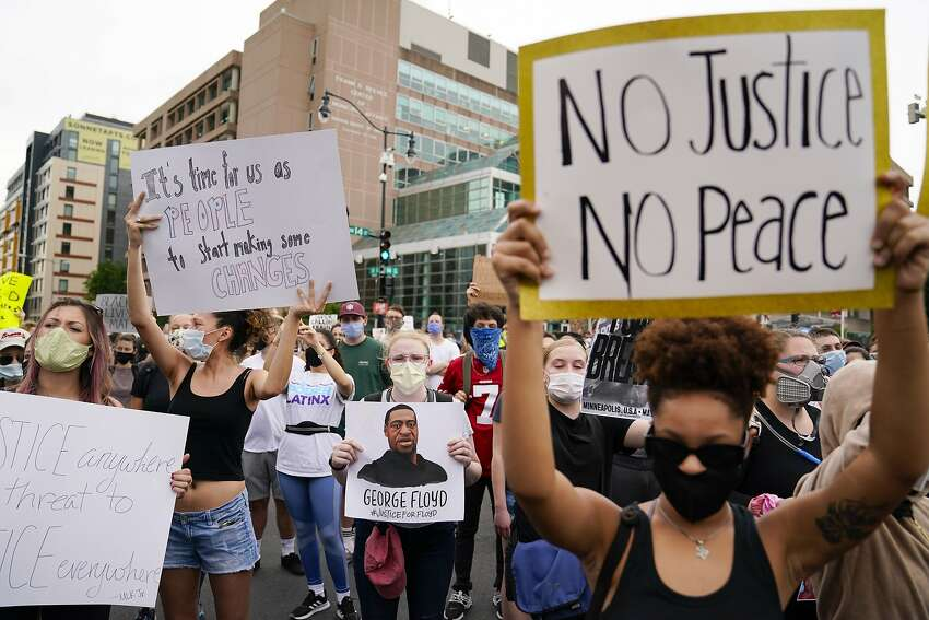 Demonstrators gather to protest the death of George Floyd, a black man who died in police custody in Minneapolis, at the corner of 14th and U streets in Washington, Friday, May 29, 2020. (AP Photo/Evan Vucci)
