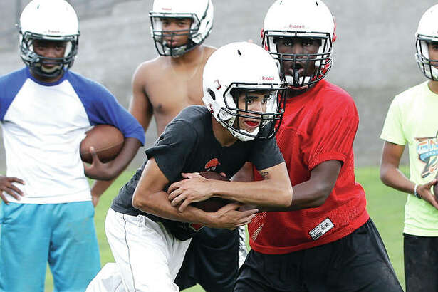 Alton's Charles Miller III, right, hands the ball off to Marcus Rounds during 2018 practice. Alton football coach Eric Dickerson and the state's other prep sports coaches are awaiting word Monday from the IHSA on the possible restoration of summer contact hours, which had been canceled earlier because of the coronavirus pandemic.