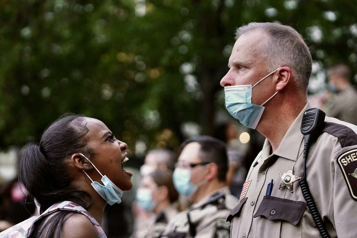 A woman yells at a sheriff's deputy during a protest following the death of George Floyd at the hand of Minneapolis policeofficers, Thursday, May 28, 2020, in Minneapolis.