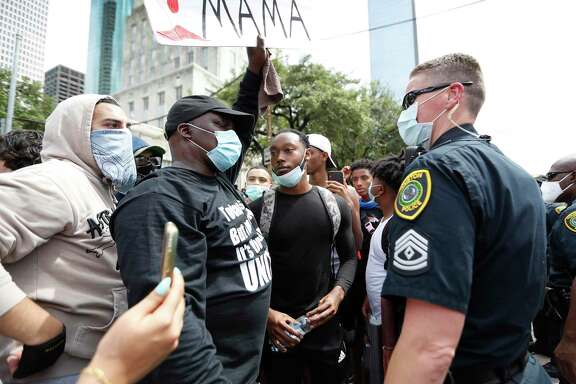 Protesters face off against Houston Police officers on Bagby Street as Black Lives Matter Houston protesters marched for George Floyd, in Houston Friday. While conversations about race, police and how to protect yourself are often commonplace for families of color, parents still need to teach their children that police officers are here to protect and serve, said Dr. Kathy Flanagan.