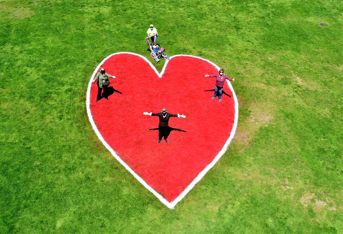 New Haven, Connecticut - Tuesday, May 5, 2020: John Sehl, a City of New Haven Parks, Recreation and Trees foreman who painted a 30-foot-high heart on the New Haven Green grass near the flag pole, top, with Geri Mauhs, chairperson of the Friends of the Green New Haven, left, David Newton, a member of the Proprietors of the Common and Undivided Lands, the five-member, self-perpetuating group that owns the Green,bottom center, and Christy Hass of Middlefield, a consultant to the Proprietors of the New Haven Green, right, stand on the heart they created as a collaborative effort to thank all those who have worked on the front lines of the COVID-19 pandemic, including those who keep essential businesses and services going and all those who are following the guidance to stay at home, keep their distance and wear masks in public. Hass, a former deputy director of the city Department of Parks, Recreation and Trees, was given the job of turning the idea into reality. She knew the city had a paint sprayer for its athletic fields, but didn't have any red field paint. The town of Rocky Hill, where she once worked, donated the 10 gallons of paint.
