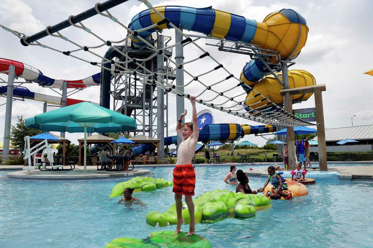 Zach Hartford, 7, reaches for the rope ladder as he attempts to cross on alligator floats at the Howdy Hollow exhibit at Typhoon Texas .