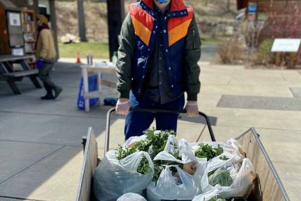 A volunteer Nick Hurwitz-Goodman loads up food shares at Common Ground high school and urban farm in New Haven, Conn.