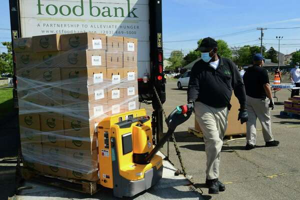 Volunteers load food into vehicles lined up for the Connecticut Food Bank Drive-Thru Mobile Pantry event Thursday, May 14, 2020, at Veteran's Memorial Park in Norwalk, CT. on This becomes the largest massive relief effort the organization has ever done following last week's successful distribution in Bridgeport, CT. In conjunction with the City of Norwalk, the Connecticut Food Bank is planning to distribute approximately 39 TONS of food at the event. This food distribution will equal approximately 61,000 meals.