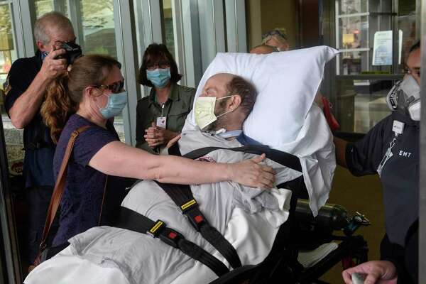 John Reed, deputy fire chief from New Rochelle, N.Y., gets a hug from his wife Suzanne after being discharged from Danbury Hospital Friday afternoon. Reed was in the hospital 56 days battling the coronavirus.