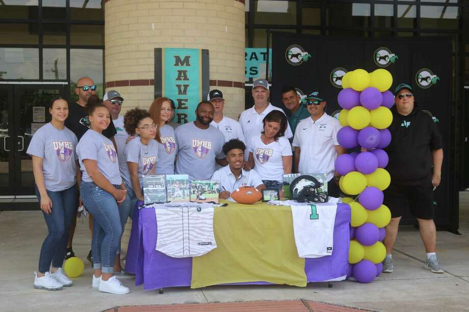 Surrounded by coaches and family, Jordan See extended his playing days by signing with the University of Mary Hardin-Baylor. Photo: Robert Avery