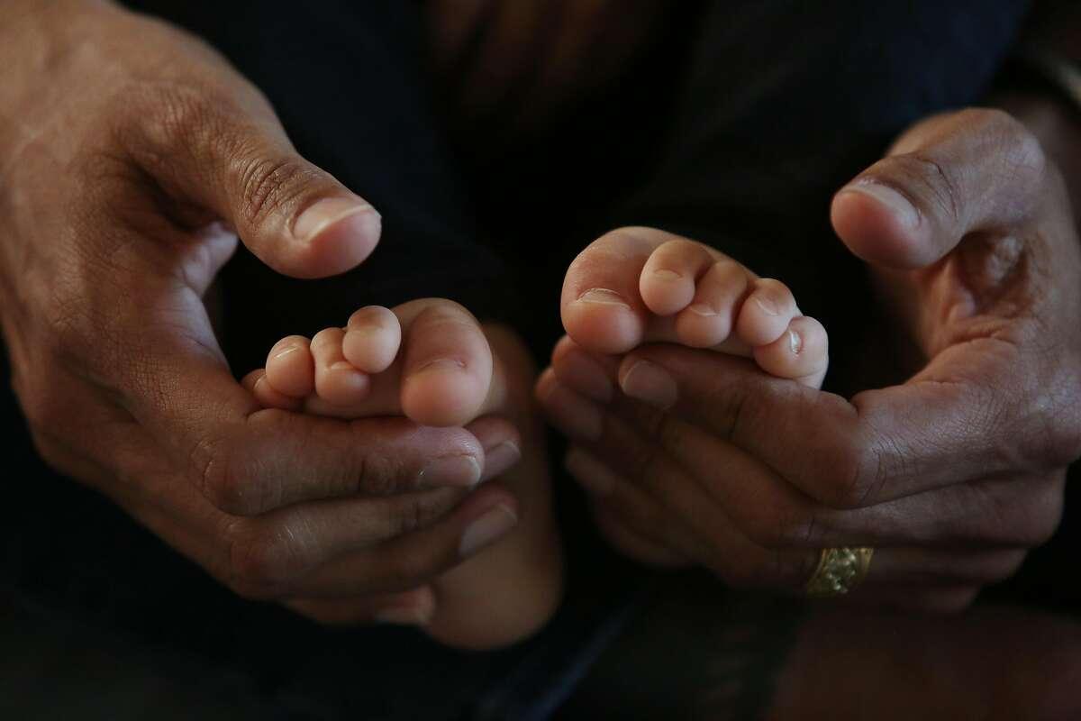 Michael Franti cradles his the feet of his 17-month-old son, Taj Franti, at their San Francisco home on Feb. 10.