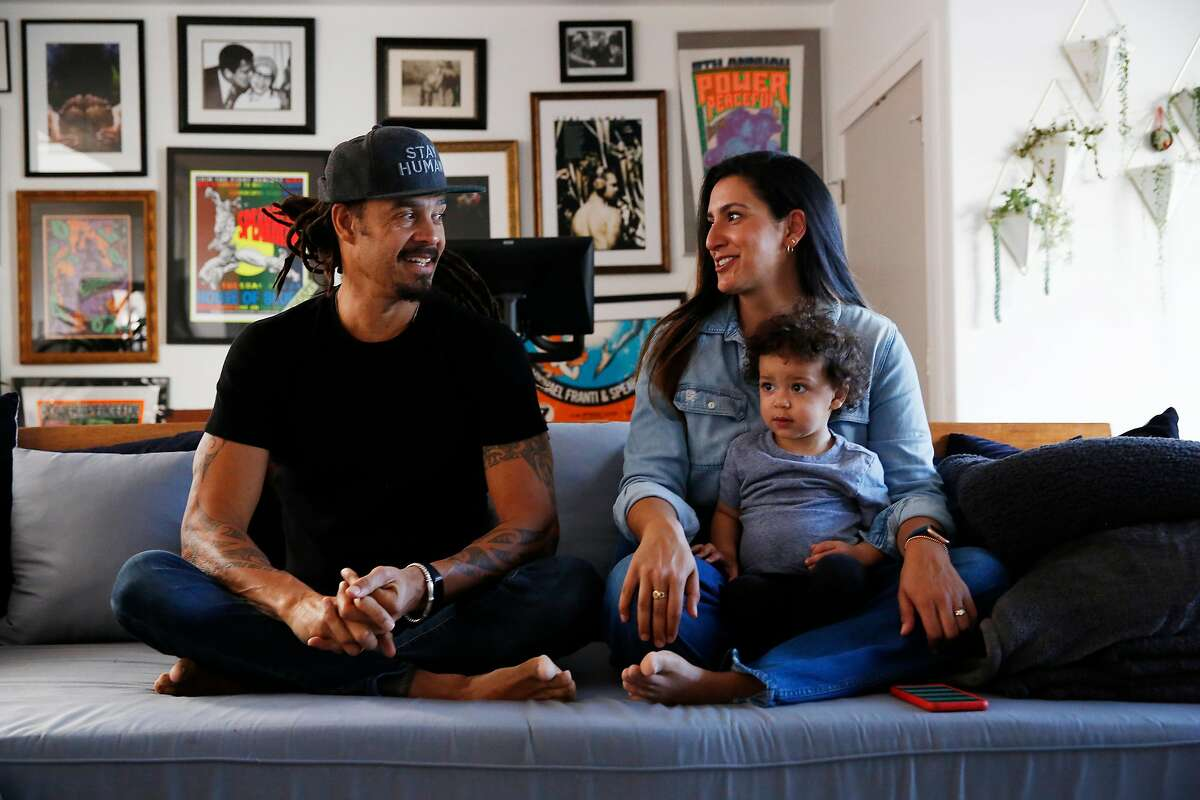 Michael Franti (left) and Sara Agah Franti (back right) sit with their son Taj Franti (front right), 17 months, as they talk during an interview at their home on Monday, February 10, 2020 in San Francisco, Calif.