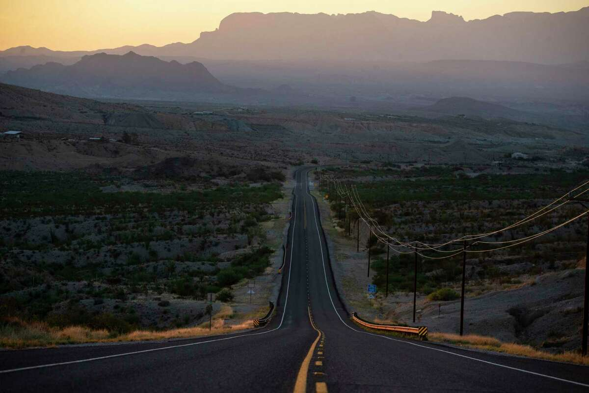 The Chisos Mountains rise in the distance past FM 170 outside of Terlingua early in the morning of May 27, 2020.