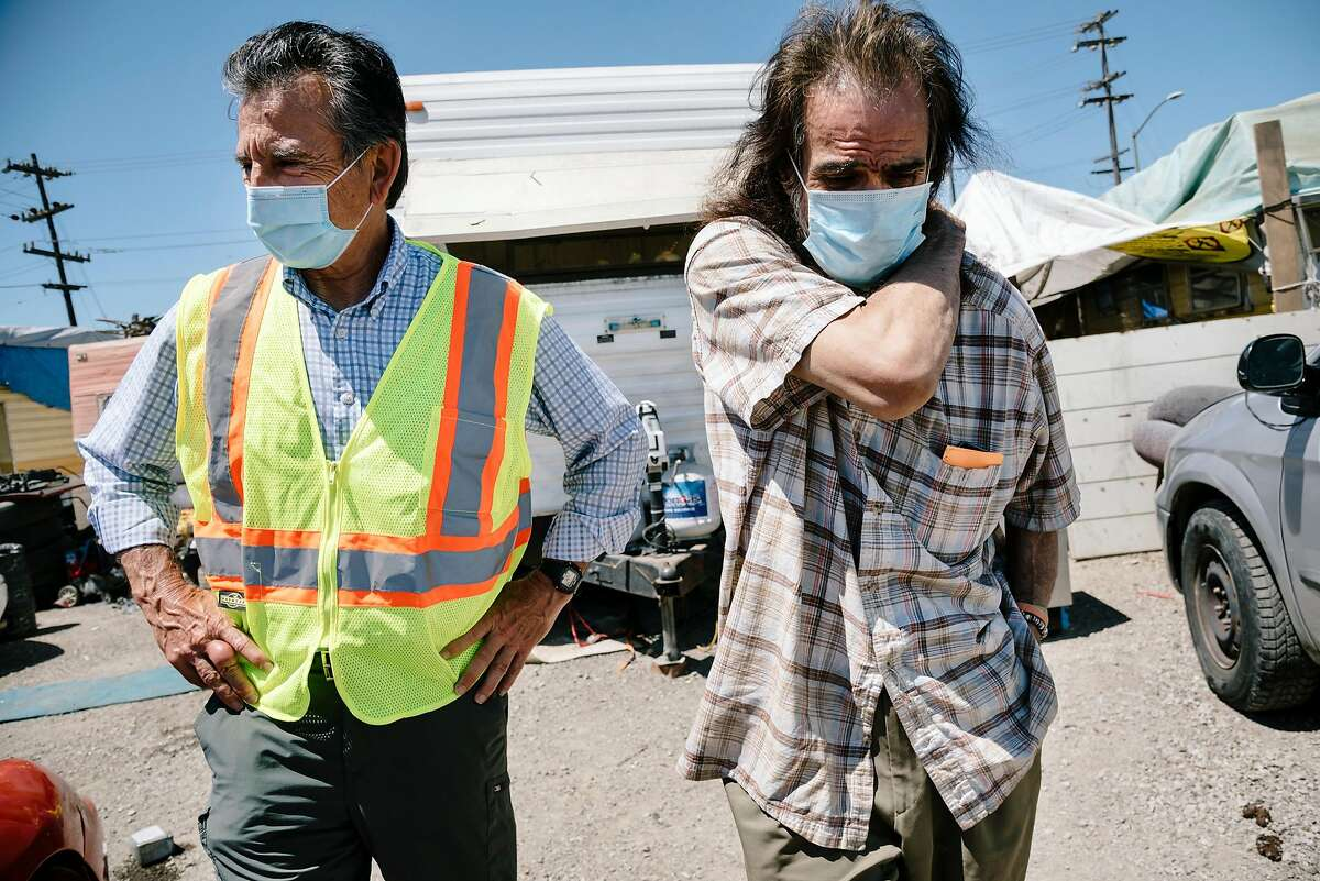 Oakland city council member Noel Gallo, left, talks with Gilberto Gonzales, who lives at the High Street Homeless Encampment in Oakland, Calif, on Thursday, May 28, 2020. Gallo said 12 recent cases of Covid-19 have been linked to the encampment through contact tracing.