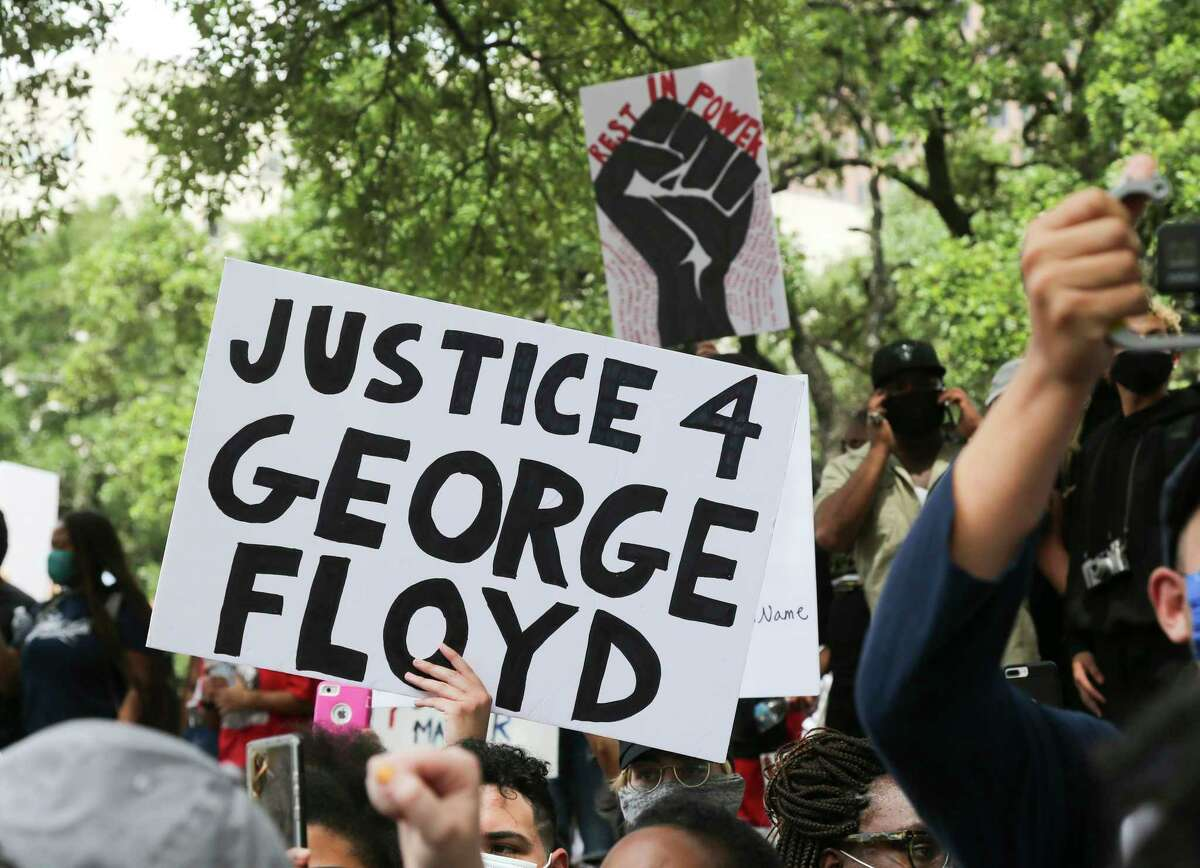 Protesters hold signs for George Floyd during a rally at Houston's City Hall on Friday, May 29, 2020.