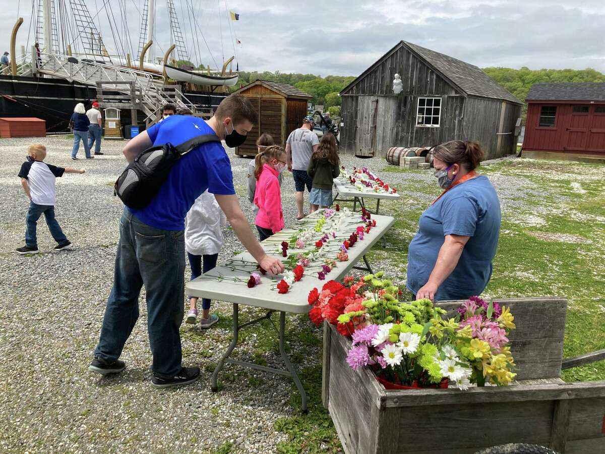 Mystic Seaport Museum was closed for more than two months because of the pandemic, but has finally reopened. Masks are required if you'd like to enjoy the premises. Visitors are seen here over Memorial Day weekend, selecting flowers to drop in the river as a tribute to U.S. veterans.