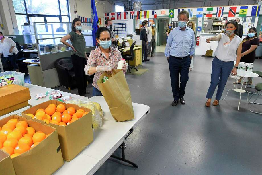 At right, Executive Director Catalina Horak walks with Connecticut Gov. Ned Lamont as they look at the many items available from Building One Community's pantry. Lamont and Lt. Gov. Susan Bysiewicz visited Building One Community in Stamford, Connecticut on May 29, 2020. B1C will offer coronavirus testing on Friday. Photo: Matthew Brown / Hearst Connecticut Media / Stamford Advocate