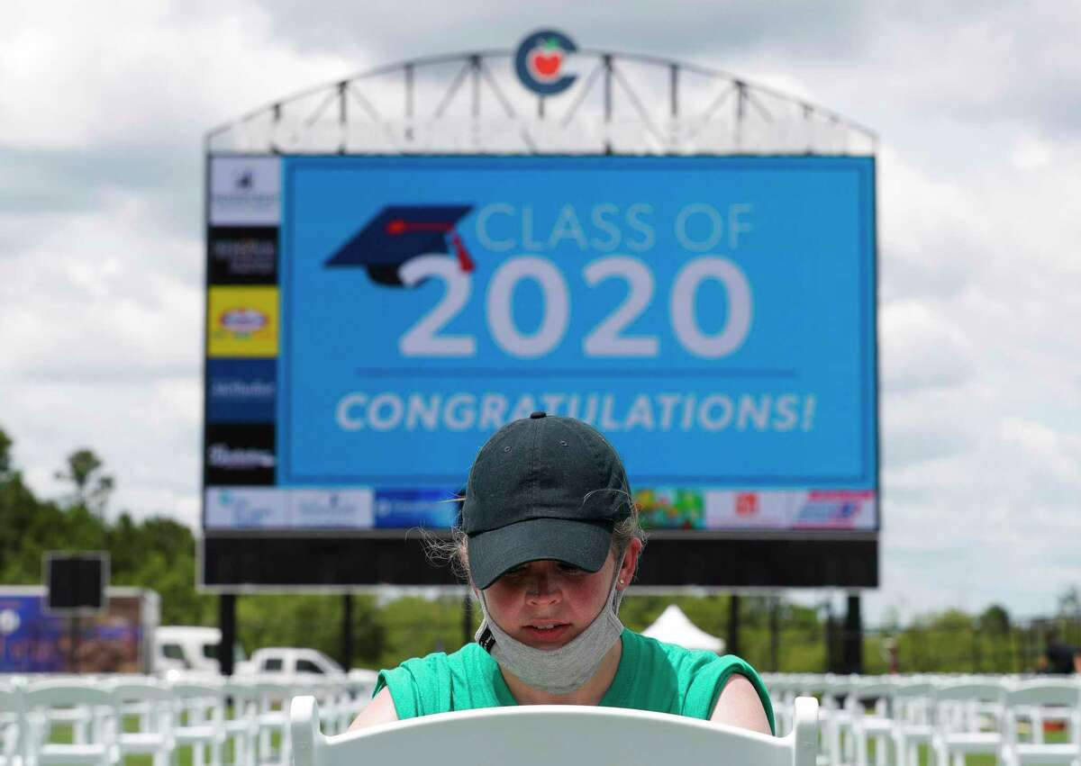Sarah Blakelock, director of communications for Conroe ISD, places sticker to help students find their seat at Woodforest Bank Stadium, Friday, May 29, 2020, in Shenandoah. Conroe ISD will hold 10 separate graduation ceremonies between its five high schools beginning Monday with Hauke High School at 8:00 a.m. with social distancing and other safety measures.