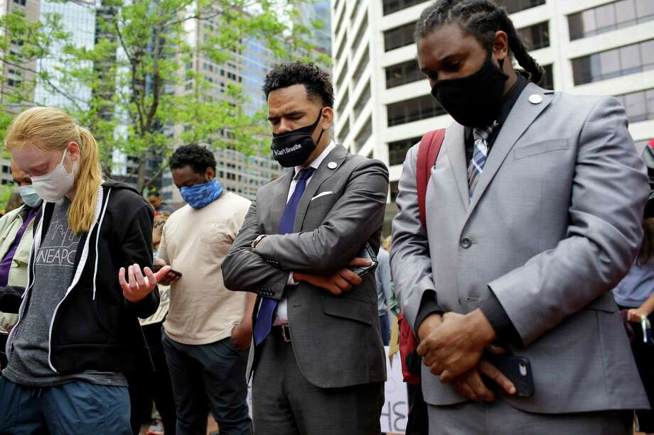 Protesters pray outside the Hennepin County Government Center in Minneapolis. Demonstrations took place across the country this week after the death of George Floyd, a black man who had been pinned to the ground by a police officer kneeling on his neck. Photo: Photo By Joshua Lott For The Washington Post / For The Washington Post