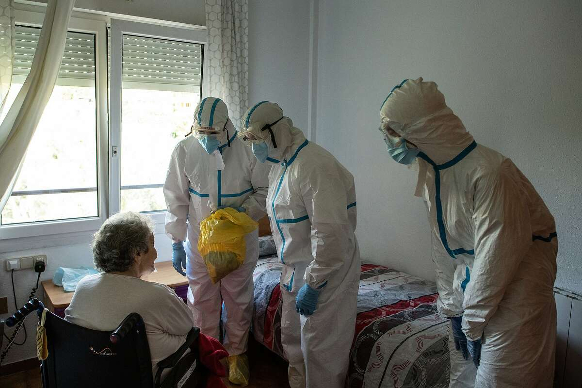 Primary health care nurse Jose Dominguez (L) and physician Joan Maria Farré (C) both in personal protective equipment (PPE) speak with Lucia Aguiló who is in quarantine after being tested positive of COVID-19 during a monitoring visit to COVID19 patients at Yayo Toni on May 21, 2020 in Pallejà, Spain.