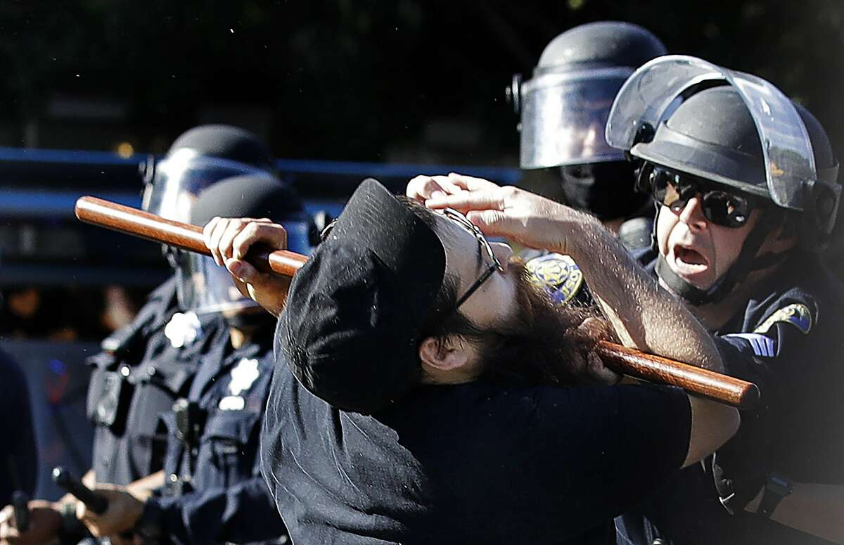 A San Jose police office strikes a protester with a baton during a protest in May.