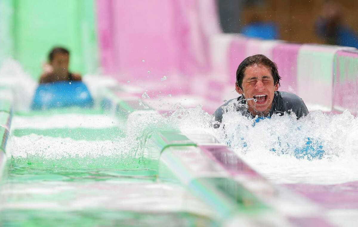 Ethan Marx, center, shares a laugh after racing friends and family down a water slide at Big Rivers Waterpark, Saturday, May 23, 2020, in New Caney.