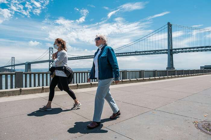 Two pedestrians walk along the Embarcadero while only one uses a mask in San Francisco on Friday, May 29, 2020.