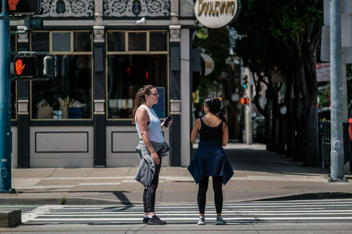 Two unmasked women stand close to each other and chat while waiting to cross the street in San Francisco on Friday, May 29, 2020.