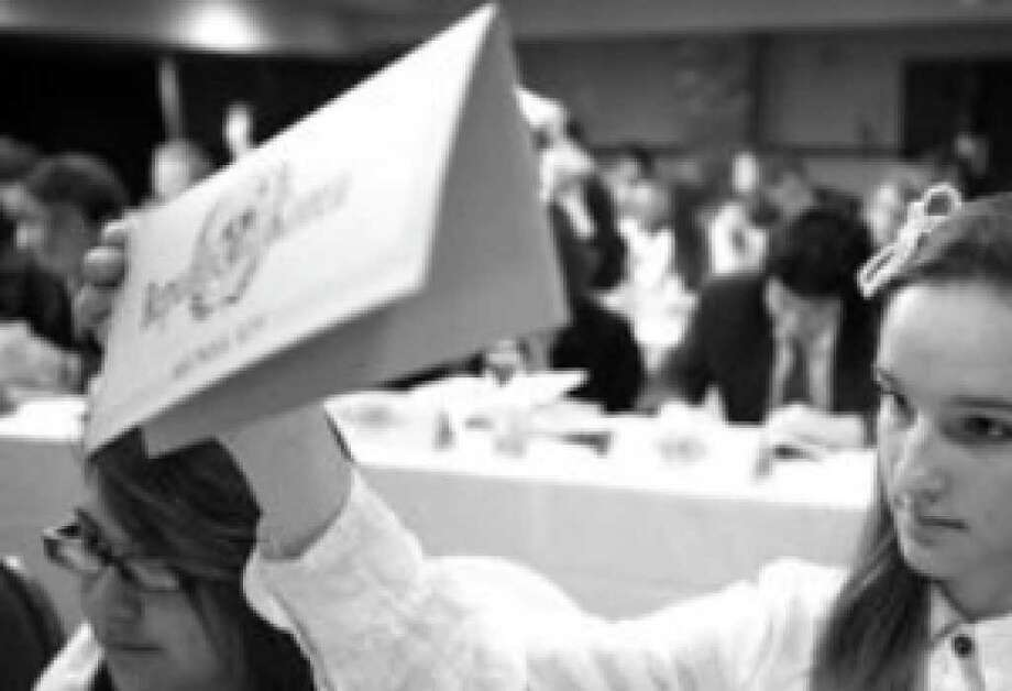 Annabella Cavello of the Liberal Arts and Science Academy in Austin raises her country's placard in order to ask a question during Model United Nations San Antonio conference.