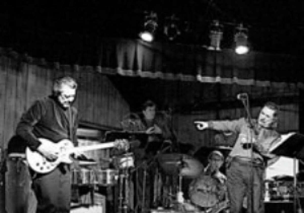 Steve Barrera (from left) Mike Jackson and Mark Luitjen perform with their band, the Court Jesters, which features two judges among its members. The group played during a benefit for Elf Louise at the Leon Springs Dance Hall.