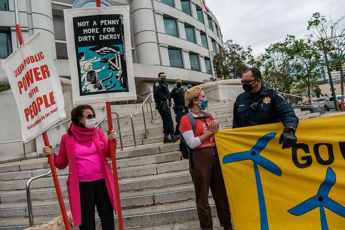 A CHP officer asks a protester to vacate the steps where she is protesting in San Francisco, Calif. on Wednesday, May 20, 2020. A small group of people had gathered to protest against a PG&E bailout.