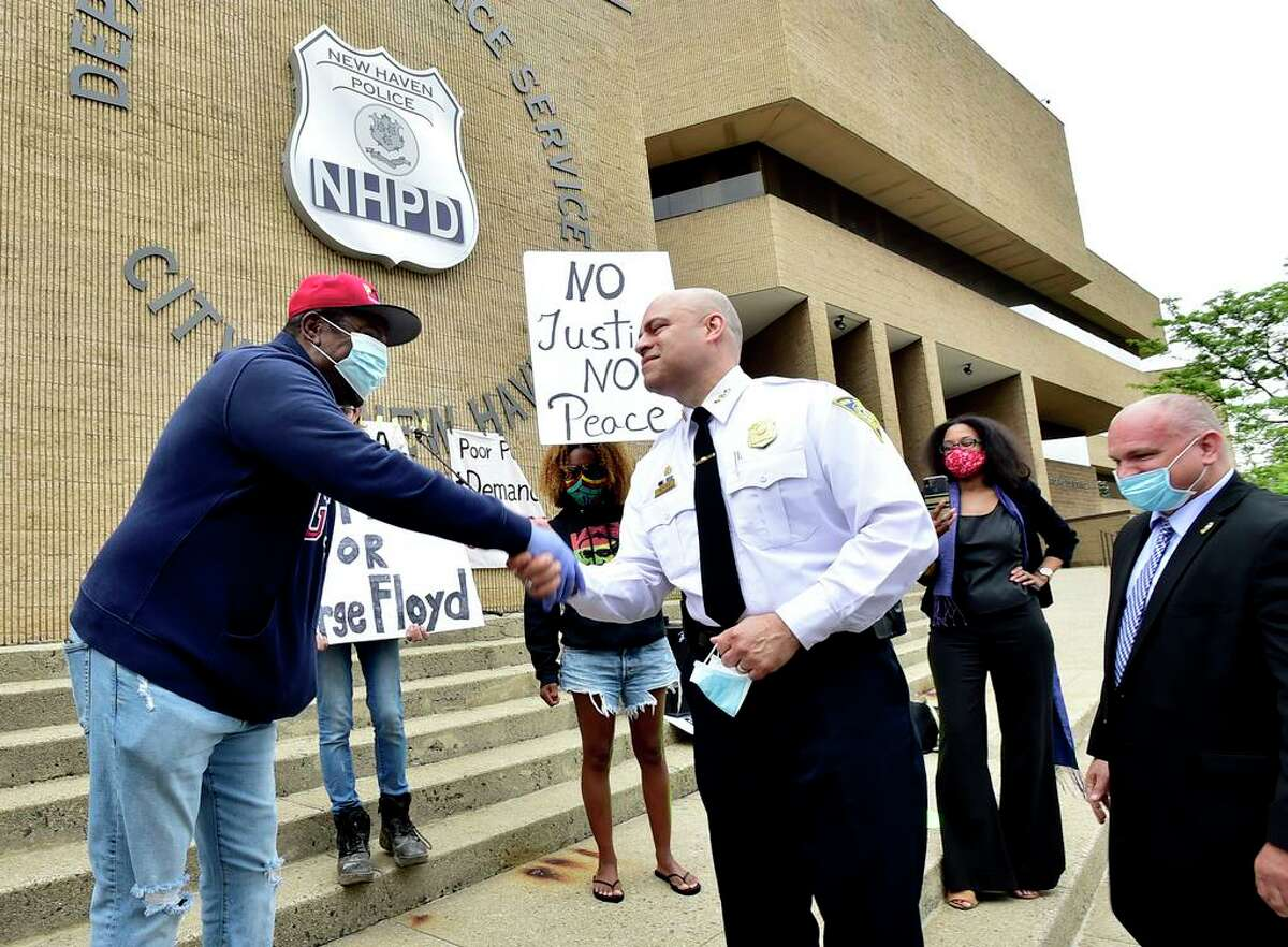 New Haven, Connecticut - Friday, May 29, 2020: Community activist Harvey Fair of New Haven, left, and New Haven Police Chief Otoniel Reyes shake hands on a positive note after a demonstration Friday in front of the New Haven Police Department that attempted to speak out against Chief Reyes and his recent comments made to the New Haven Register, police brutality, and prison abuses. Chief Reyes shared his sentiments with demonstrators explaining his leadership role in the police department and the role of the police protecting New Haven.