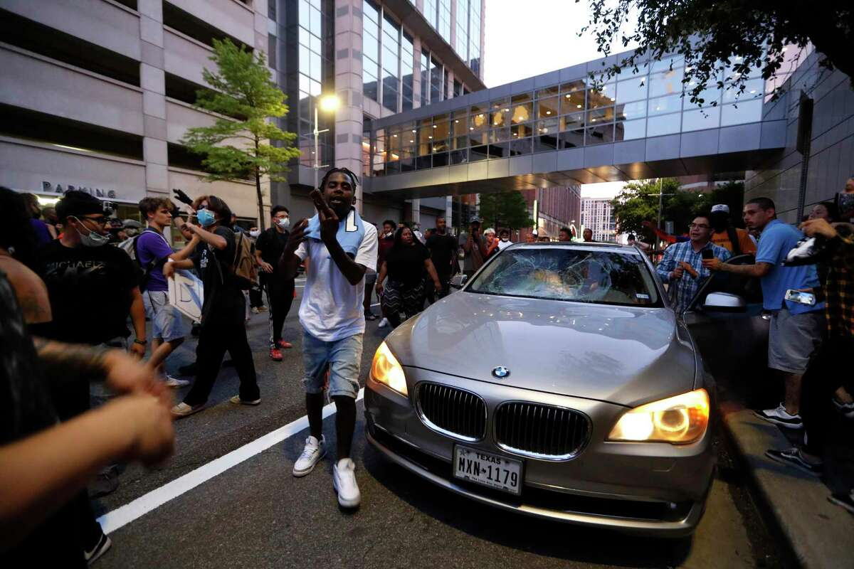 Protesters break the windows of a BMW downtown as Black Lives Matter Houston protested the death of George Floyd, in Houston, Friday, May 29, 2020. Floyd the man originally from Houston, who died while he was in the custody of Minneapolis police earlier this week, which has sparked protests throughout the country.
