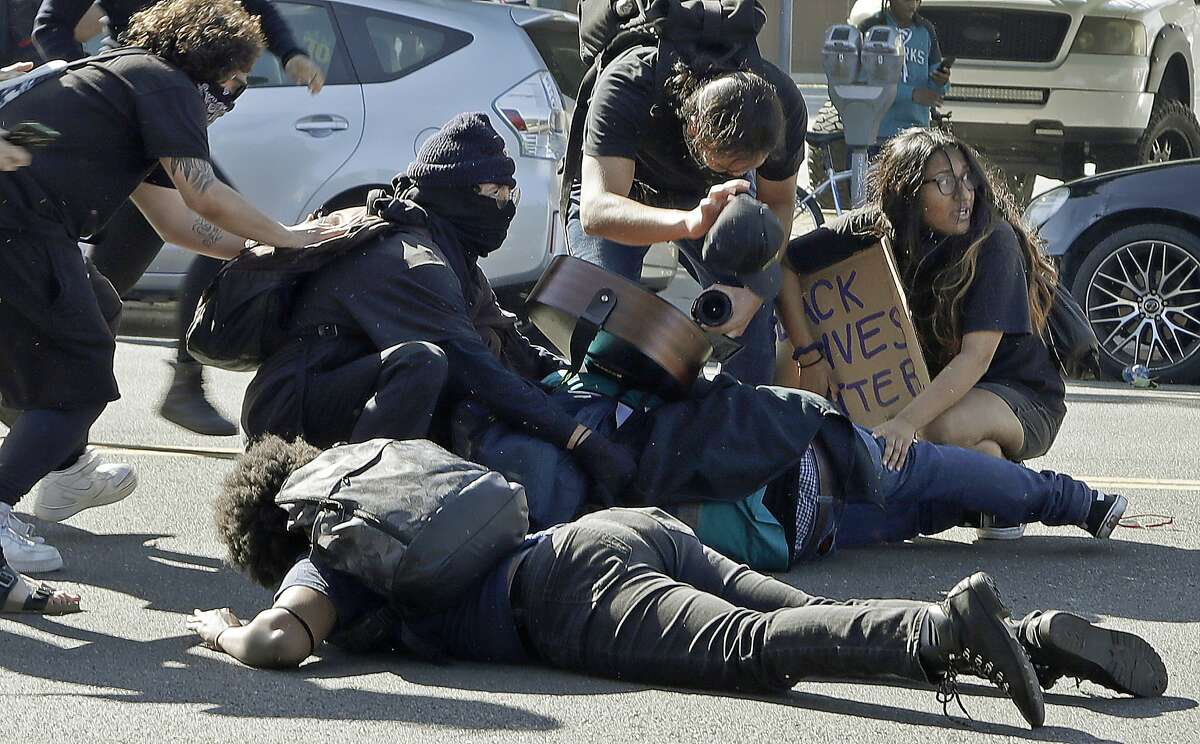 Protestors cover one another as San Jose police fire projectiles at them on Friday, May 29, 2020, in San Jose, Calif.