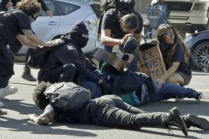 Protestors cover one another as San Jose police fire projectiles at them on Friday, May 29, 2020, in San Jose, Calif. (AP Photo/Ben Margot)