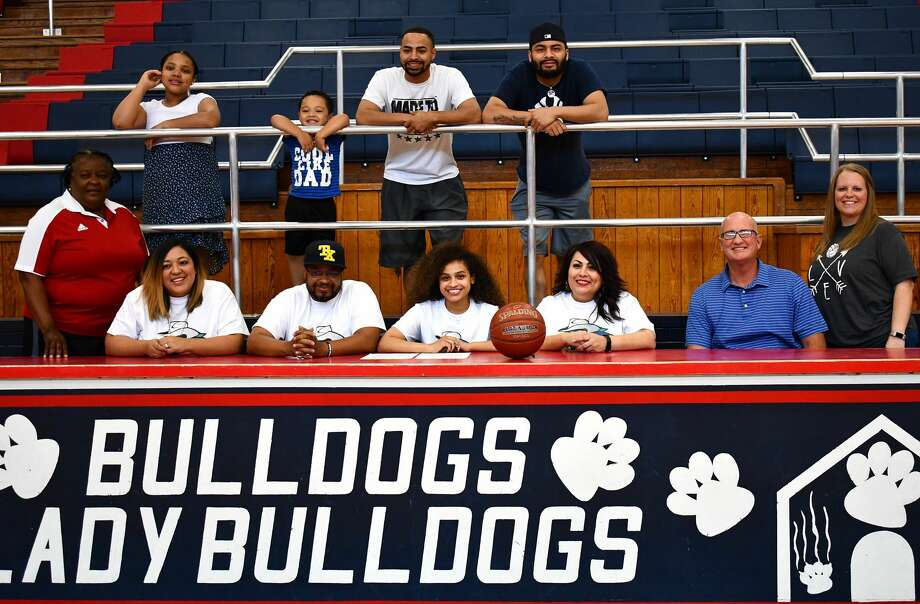 Plainview senior Osen Ellis (middle) is joined by family and coaches as she officially signs her Letter of Intent to continue her basketball career with Western Texas College in an intimate ceremony on Thursday night in the Dog House. Photo: Nathan Giese/Planview Herald