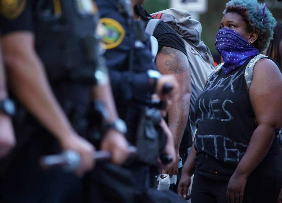 A woman confronts Houston Police Officers as they line up on Travis and Clay Streets in downtown Houston on Friday, May 29, 2020.