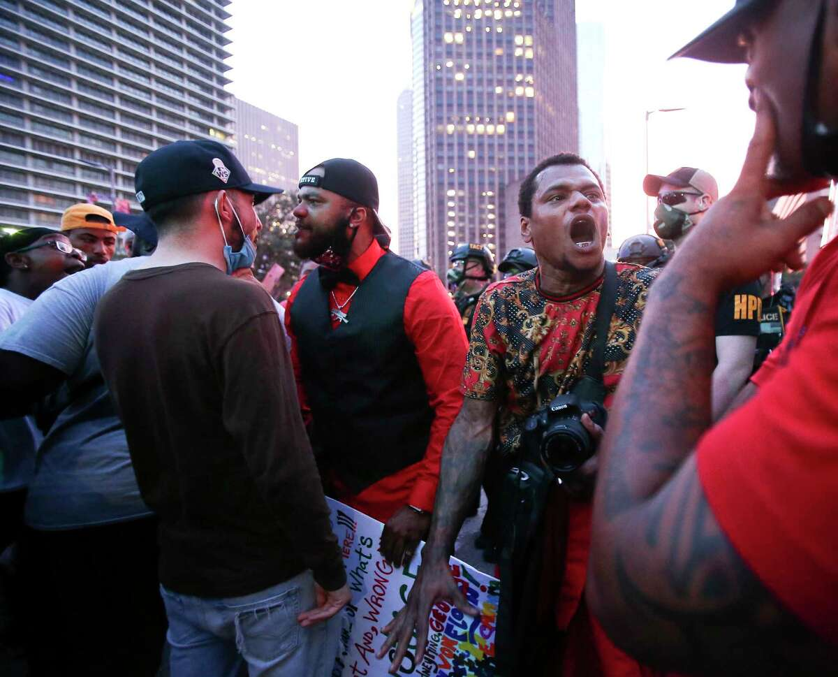 Some protesters try to calm down the crowd as they gather in front of a line Houston Police on Clay and Travis Streets in downtown Houston on Friday, May 29, 2020.