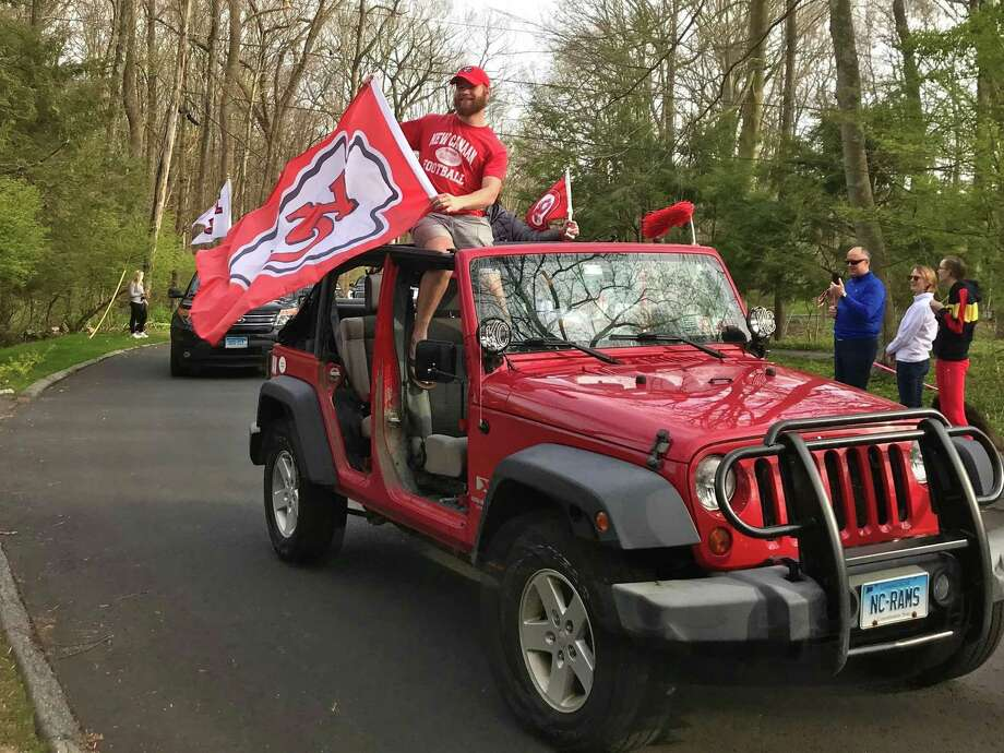 A Jeep drives by the Niang house on Saturday, April 25, 2020, waving a Kansas City Chiefs flag after New Canaan alum Lucas Niang was drafted by the the NFL team the day before. New Canaan, Conn. Photo: Scott Ericson / Hearst Connecticut Media / Connecticut Post