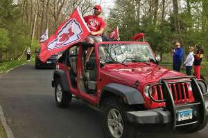 A Jeep drives by the Niang house on Saturday, April 25, 2020, waving a Kansas City Chiefs flag after New Canaan alum Lucas Niang was drafted by the the NFL team the day before. New Canaan, Conn.