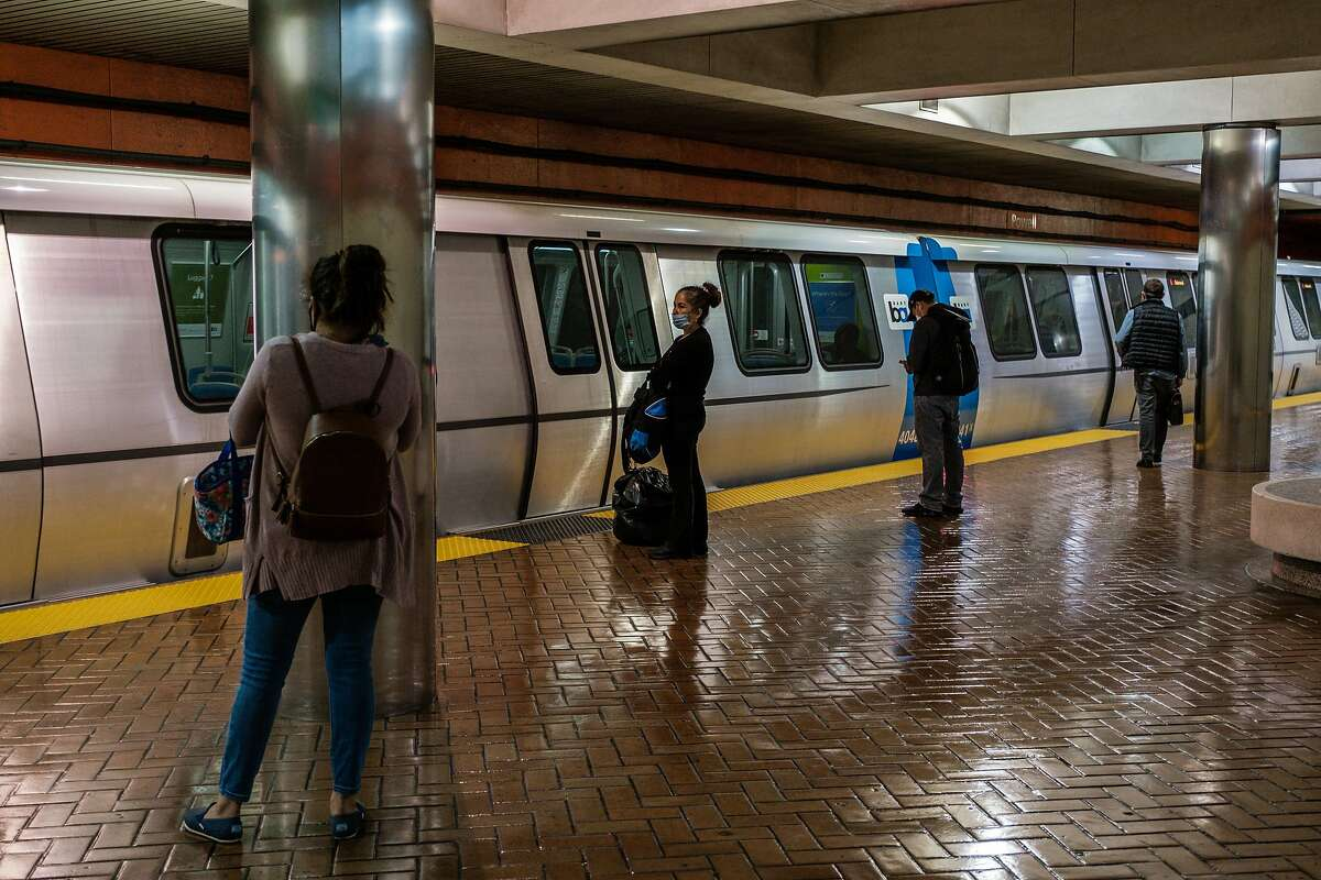 People keep their distance from each other on the Powell Street Bart station in San Francisco on Wednesday, May 27, 2020.