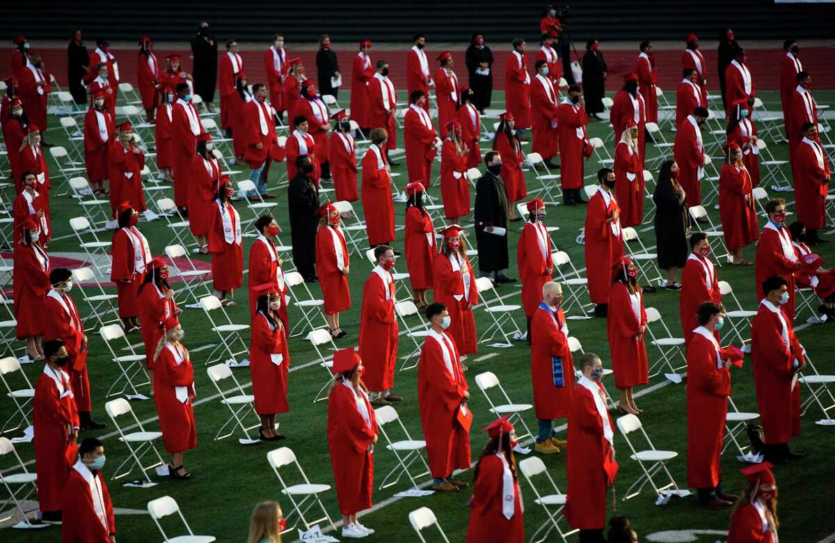 Crosby High School seniors stand for the Pledge of Allegiance during their commencement ceremony on Friday, May 29, 2020, in Crosby. The graduates' seating area was spread apart as a precaution measure because of the COVID-19 pandemic.
