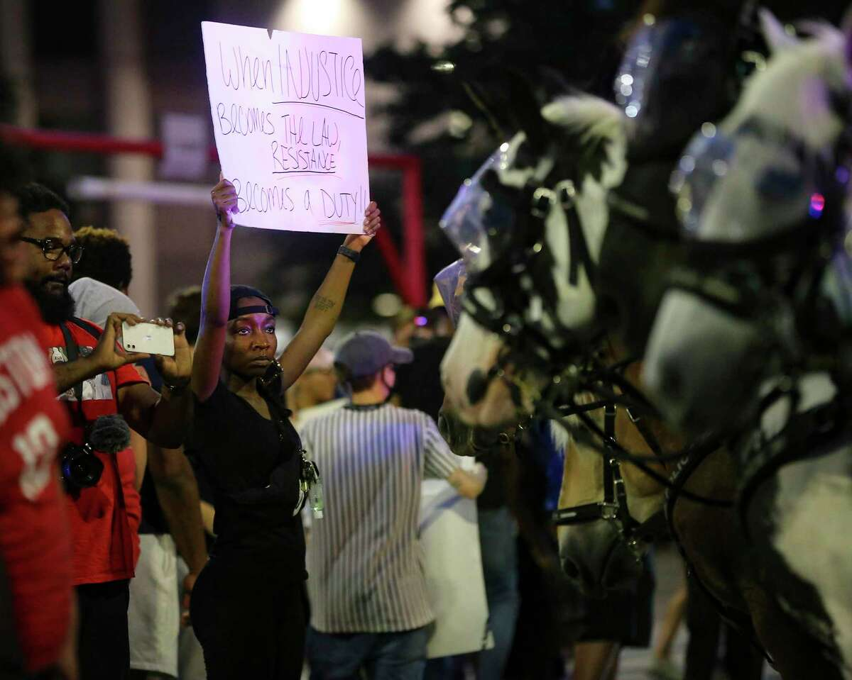 A woman holds a sign in front of a line of police horses on Travis Street in downtown Houston on Friday, May 29, 2020.