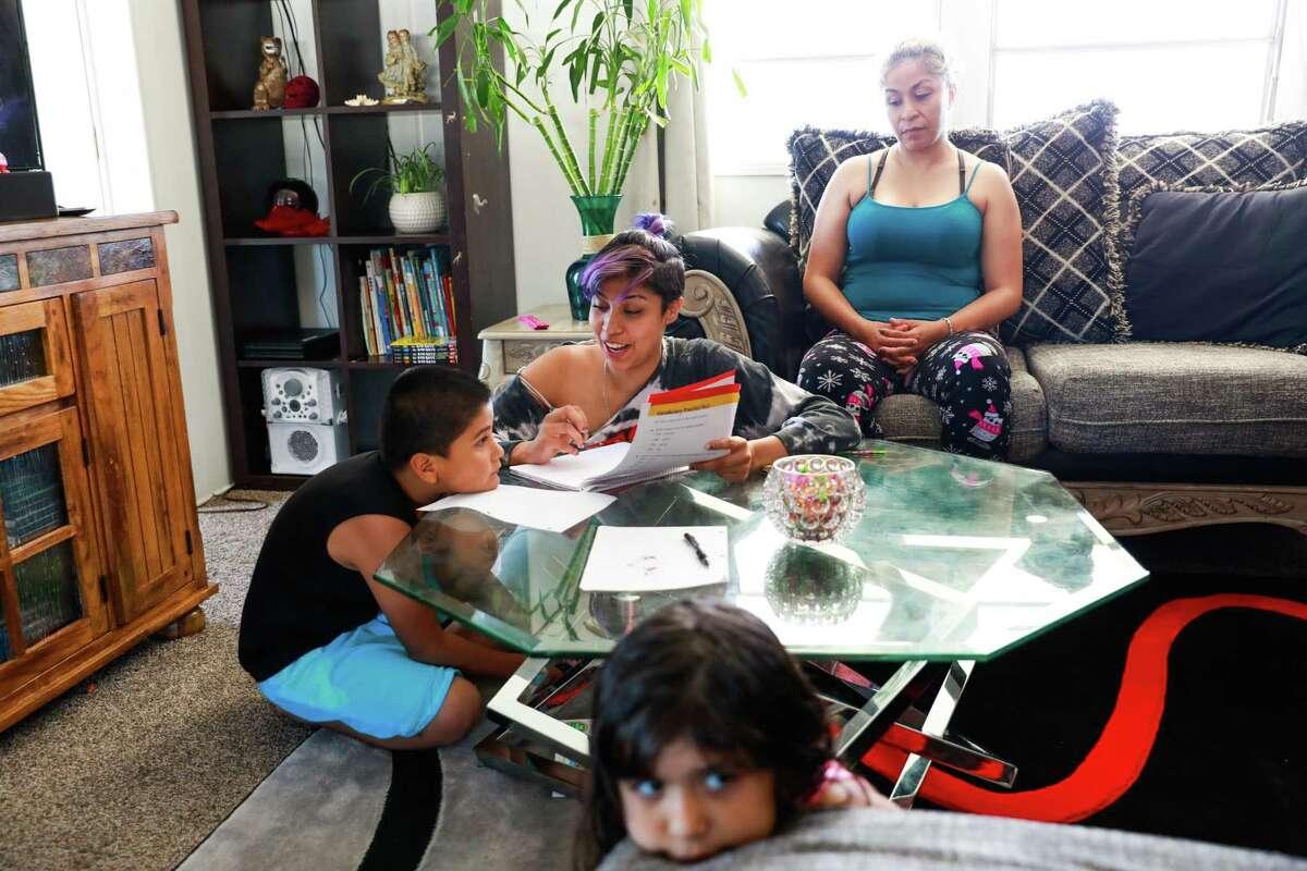 Briza Moreno, 19 (center), helps her brother Gael Ayala, 7, at home with mom Miriam Moreno and sister Kimberly Ayala, 6.