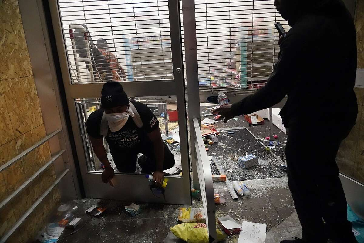 People break into a closed Walgreen's at 14th and Broadway streets in Oakland, Calif., after protests to the killing of George Floyd by Minnesota police earlier in the week turned violent on Friday, May 29, 2020.