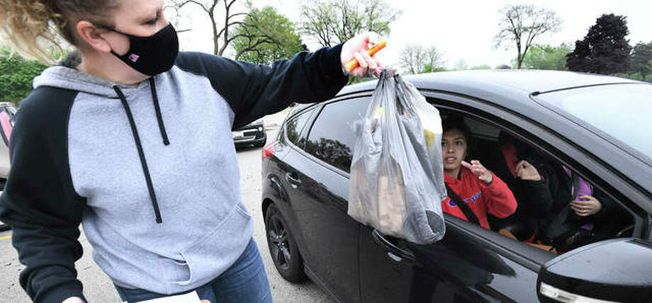 Connie Graska of the Addison Children's Center and the Metropolitan Family Services hands Angela Flores, 15, and her mother, Maria, of Hanover Park, diapers and pasta for them and other families in need of these staple items. Photo: Mark Welsh | Daily Herald (AP)
