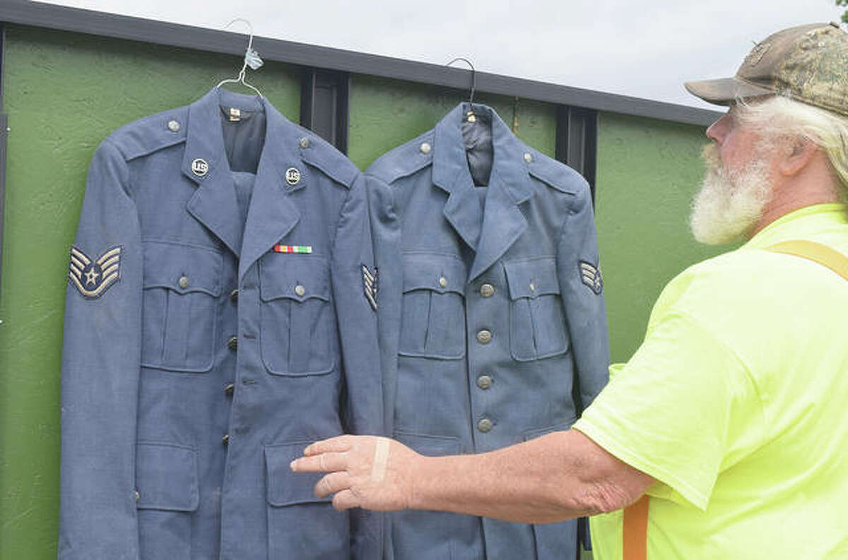 Mac Davenport examines two Air Force uniforms he found while cleaning up a Jacksonville building.