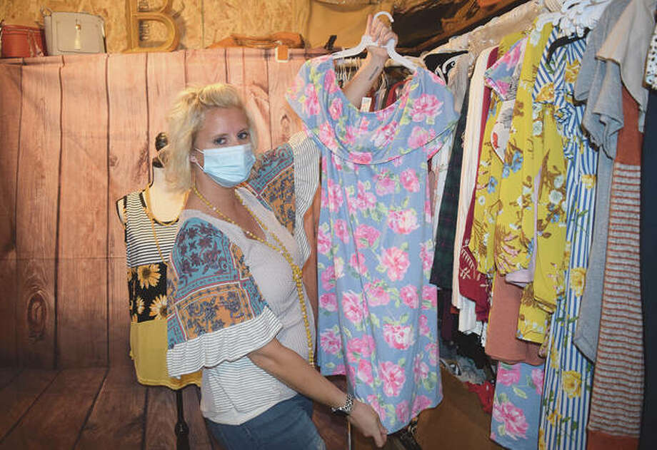 Kayla Anders West, owner of Blondie's Boutique in Murrayville, shows off one of the dresses she has in stock. West organized a T-shirt fundraiser to support local businesses that had to close their doors because of the COVID-19 pandemic. Photo: Marco Cartolano | Journal-Courier