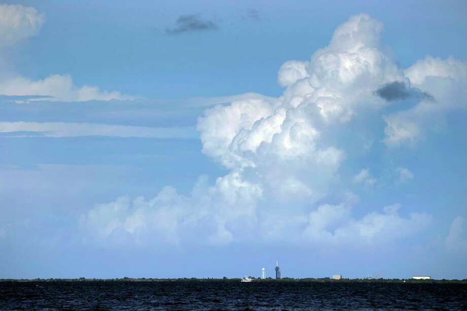 The SpaceX Falcon 9, with Dragon crew capsule on top of the rocket, is dwarfed by storm clouds building in the distance as it sits on Launch Pad 39-A, Friday, May 29, 2020, at the Kennedy Space Center in Cape Canaveral, Fla. Two astronauts will fly on the SpaceX Demo-2 mission to the International Space Station currently scheduled for launch weather permitting on Saturday, May 30. For the first time in nearly a decade, astronauts will blast into orbit aboard an American rocket from American soil, a first for a private company. Photo: Charlie Riedel, AP / Copyright 2020 The Associated Press. All rights reserved.