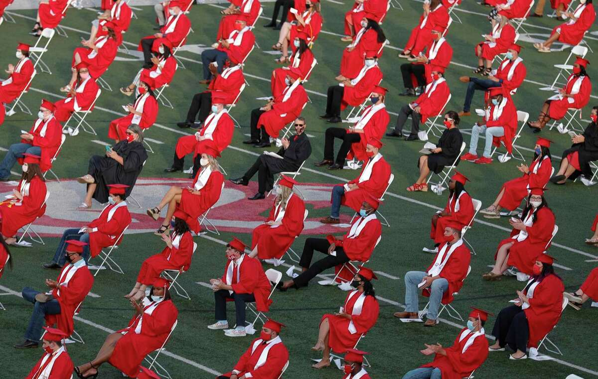 Seniors sit spaced six feet apart during Crosby High School's graduation ceremony at Cougar Stadium, Friday, May 29, 2020, in Crosby.