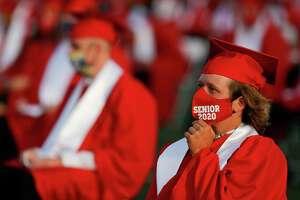 Garrett Aubain adjusts his face mask during Crosby High School's graduation ceremony at Cougar Stadium, Friday, May 29, 2020, in Crosby.