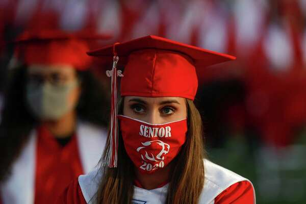 Meagan Londrigan wears a face mask during Crosby High School's graduation ceremony at Cougar Stadium, Friday, May 29, 2020, in Crosby.