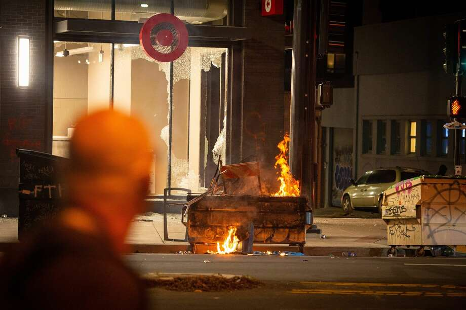 A dumpster is lit on fire infront of a Target store in Oakland California on May 30, 2020, over the death of George Floyd, a black man who died after a white policeman kneeled on his neck for several minutes. - Violent protests erupted across the United States late on May 29 over the death of a handcuffed black man in police custody, with murder charges laid against the arresting Minneapolis officer failing to quell boiling anger. Photo: JOSH EDELSON/AFP Via Getty Images